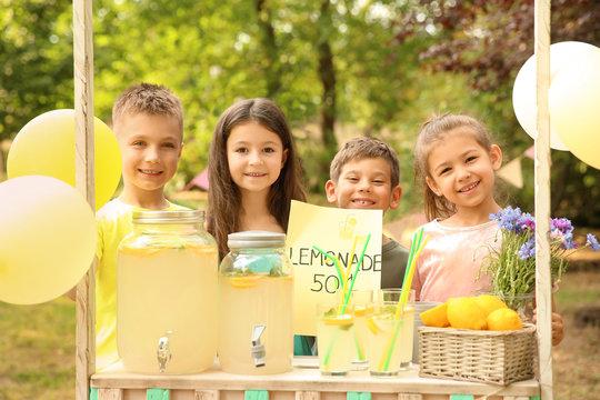Little children at lemonade stand in park