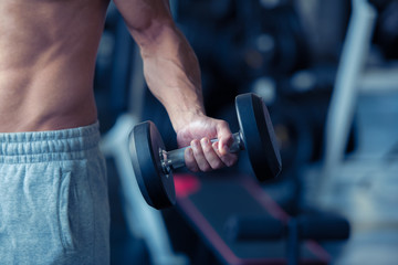 Strong bodybuilder man lifting weights in the sport gym, close up ,bodybuilding and muscle building concept.