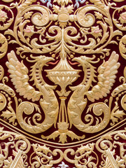 Detail of two dragons embroidered in gold on red velvet in the mantle of the Virgin of Regla, Holy Week in Seville, Spain