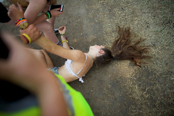 Sarah Cidina, 21, is aided by friends and emergency personnel after having too much to drink, on the fourth and final day of the Firefly Music Festival in Dover, Delaware U.S.
