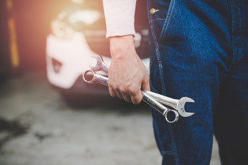 Hand of car mechanic with wrench at service center repair