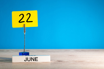 June 22nd. Day 22 of june month, calendar on table with blue background. Summer time, empty space for text or template