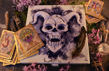 Mystic box with horned demon, tarot cards, magic objects, black candles and lilac flowers. Occult, esoteric and divination still life. Halloween background with vintage objects and magic ritual