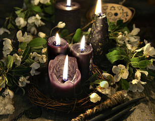 Black candles and white flowers on witch table. Occult, esoteric and divination still life. Halloween background with vintage objects and magic ritual