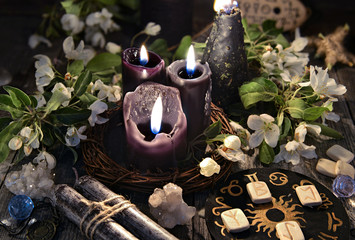 Black candles with runes, zodiac circle and spring flowers. Occult, esoteric and divination still life. Halloween background with vintage objects and magic ritual