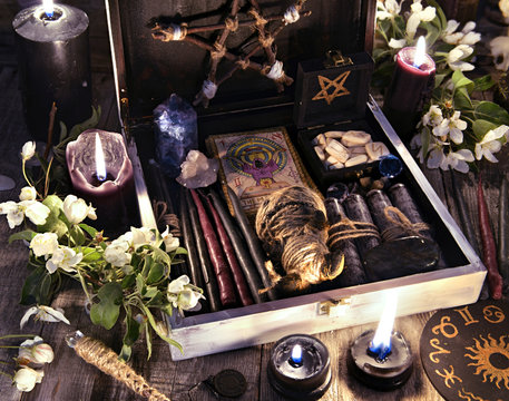 Witch box with black candles, tarot cards, runes, voodoo doll and magic objects with flowers Occult, esoteric and divination still life. Halloween background with vintage objects and magic ritual