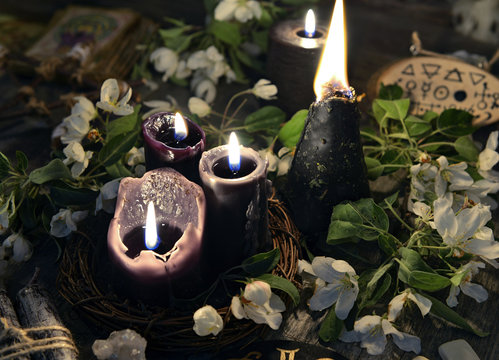 White flowers, black candles and mystic objects. Occult, esoteric and divination still life. Halloween background with vintage objects and magic ritual