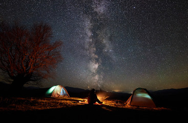 Night camping in mountains. Silhouette of male hiker sitting between two illuminated tents, enjoying campfire, beautiful starry sky and Milky way on background. Tourism, outdoor activity concept