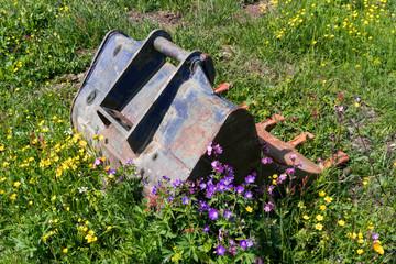 Wall Mural - old rusted excavator spoon in an overgrown wildflower meadow