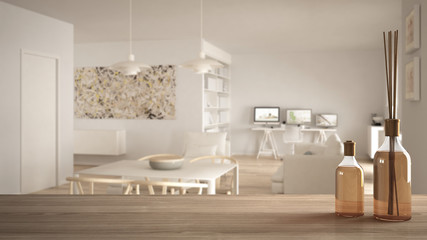 Wooden table top or shelf with aromatic sticks bottles over blurred scandinavian minimalist living room with home workplace, white architecture interior design