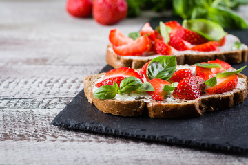 Strawberry bruschetta with cottage cheese,basil and strawberry on slate board on shabby wooden table background, copy space