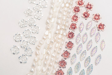Materials for creative work on a white background. Ivory pearls and silver plated and copper flower alloy charms