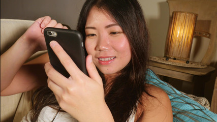 young sweet happy and pretty Asian Korean woman using internet social media app on mobile phone smiling cheerful having fun at home sofa couch