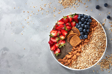 Fresh berries, almonds, oatmeal and granola in a plate with gray concrete background top view. Healthy food