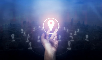 Hand holding location pin map icon and network connection on city of screen. Innovation technology concept.