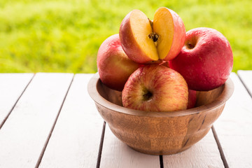 Red apples on wooden table with natural green background