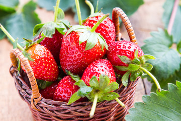 Fresh red strawberries are in a wooden basket