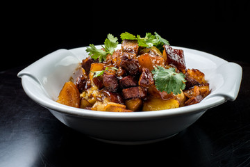 Chinese beef stew with young potatoes in sweet sauce, in white plate on black background