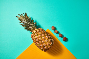 Pineapple and litchi composition on an orange-green background, top view