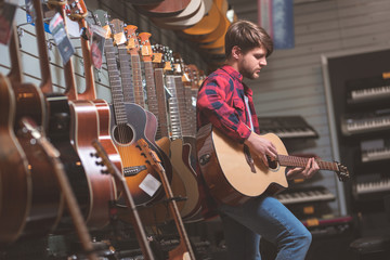 Spoed Foto op Canvas Muziekwinkel Young man playing on a guitar