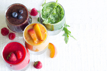 Smoothie juice with healthy fresh raw  fruits and vegetables on white planks