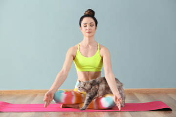 Beautiful woman with cat practicing yoga indoors