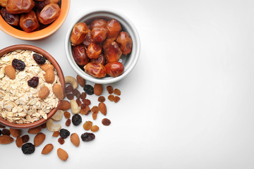 Composition with oatmeal flakes, dry fruits and nuts on white background