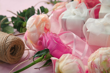 Beautiful flowers and gift boxes on color background, closeup