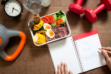 Healthy concept with nutrion food in lunch box and fitness equipments with woman writing time to get healthy on diary book