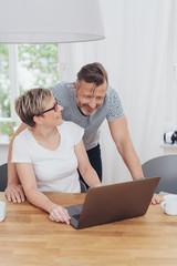 ehepaar sitzt zuhause am tisch und schaut gemeinsam auf dem laptop