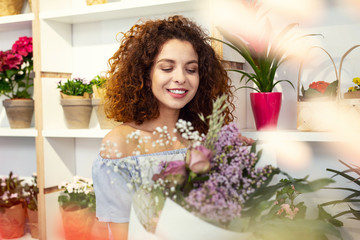 Flower paradise. Cheerful happy woman standing among flowers while looking at the bouquet