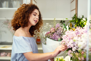 So tender. Nice pleasant woman touching flowers while being in the flower shop