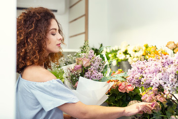 Big choice. Smart nice woman being in the flower shop while choosing a bouquet