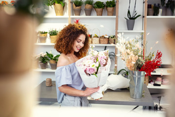 My masterpiece. Happy positive florist holding a bouquet while enjoying her work