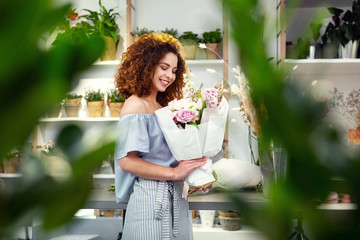 My hobby. Happy delighted woman enjoying flowers while working in her flower shop