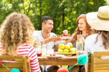 Handsome man offering fruit to his girlfriend while having a garden party with friends