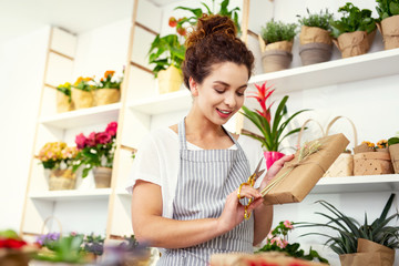 Beautiful gift. Pleasant nice woman standing in the flower shop while finishing wrapping the gift