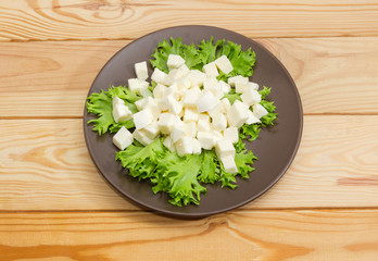 Diced mozzarella cheese on lettuce leaves on brown dish