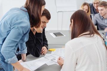 arbeitsgruppe im büro beugt sich über unterlagen und bespricht ideen