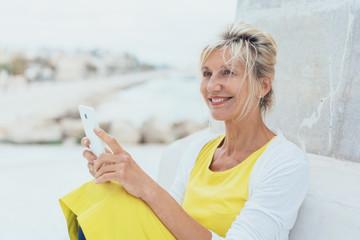 ältere dame sitzt lächelnd am strand und hält ihr handy in den händen