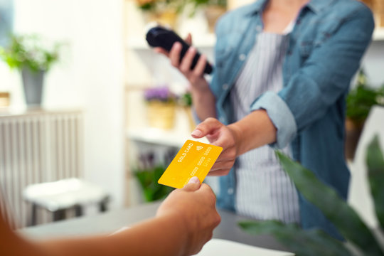 Money transaction. Selective focus of a debit card being given to the shop assistant while making a payment