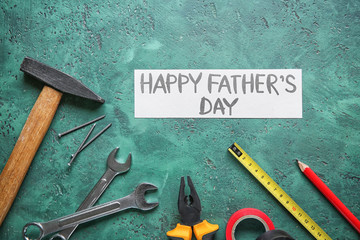 """Sheet of paper with text """"Happy Father's Day"""" and set of tools on color background"""