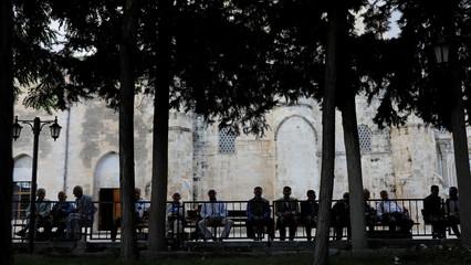 People enjoy the garden of a mosque in Silvan