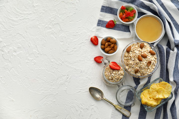 Composition with raw oatmeal, honey, nuts and strawberry on white textured background