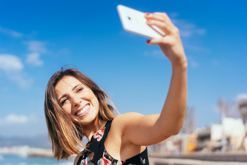 lachende frau macht ein Selfie am Strand