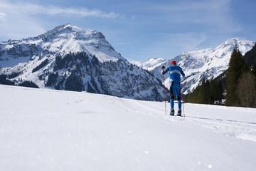Skilangläufer vor Alpenbergen im Winter beim Skifahren5