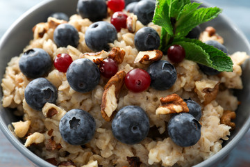 Tasty oatmeal with fresh berries and nuts, closeup