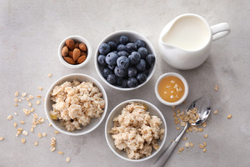 Composition with tasty oatmeal, fresh berries, milk and honey on table