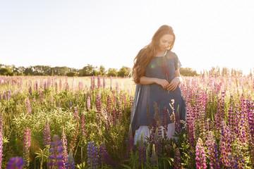 girl in blue dress walking in flower field. Horizontal portrait