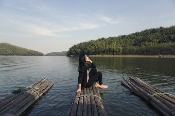 Young Asian woman sitting on bamboo river rafting in Thailand, natural view.